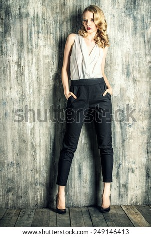 Fashion shot of a glamorous blonde woman with retro make-up and hairdo. Full length portrait. - stock photo
