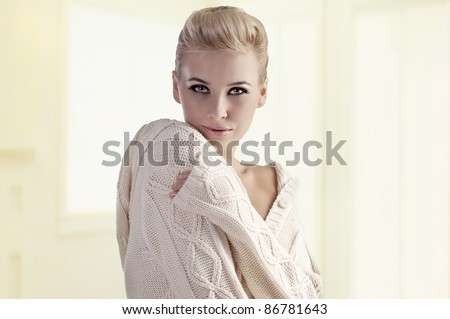fashion shot of a gorgeous blonde girl with an elegant up-do wearing a warm winter sweater - stock photo