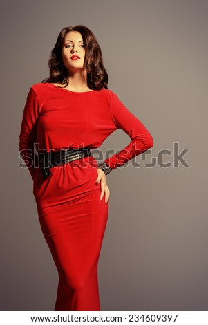 Fashion shot of a gorgeous young woman in elegant red dress. - stock photo