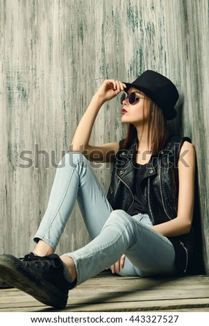 Fashion shot of a modern brunette girl with beautiful big brown eyes wearing jeans and black leather jacket. Beauty, fashion. Youth generation. - stock photo
