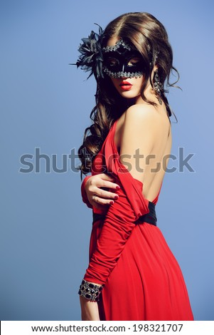 Fashion shot of a sexual  woman in elegant red dress with bare shoulder wearing ornate carnival mask. - stock photo