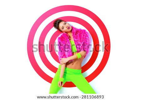 Fashion shot of a stunning female model posing in vivid colourful clothes over red target. Bright fashion. Studio shot. - stock photo