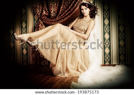 Fashion shot of a stunning woman in luxurious golden dress over vintage background. - stock photo