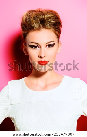 Fashion shot of a stunning young woman posing in white dress over pink background. Bright makeup. Beauty, fashion. - stock photo
