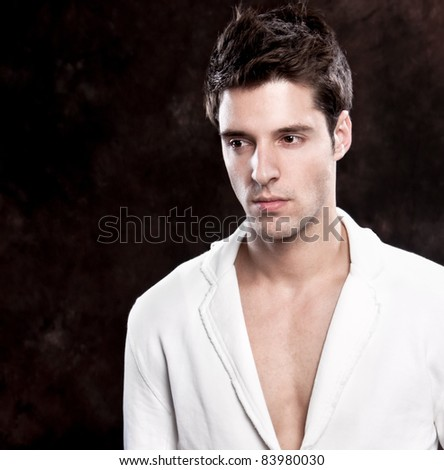 Fashion shot of a young trendy European man in white suit - stock photo