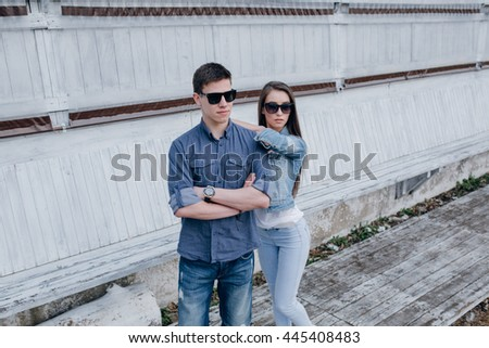 Fashion shot of an attractive young couple in jeans clothes posing outdoor - stock photo