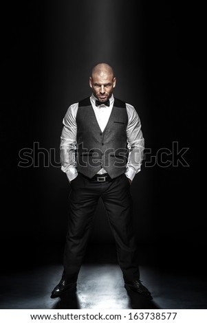 Fashion shot of an elegant young man wearing suit on black background. - stock photo