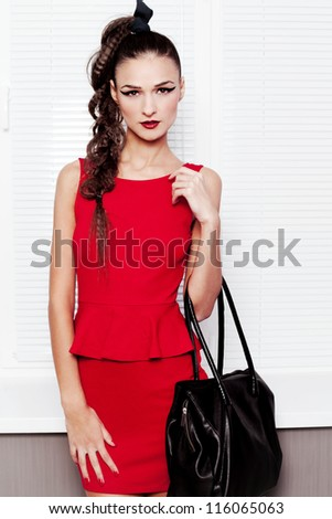 Fashion shot of beautiful girl in a red dress posing in the studio with a bag in her hand - stock photo