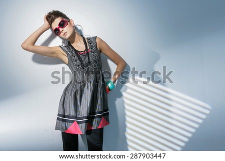 fashion shot of girl with sunglasses posing in light background  - stock photo