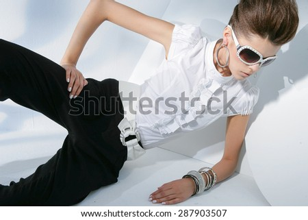 fashion shot of girl with sunglasses sitting posing in light background  - stock photo