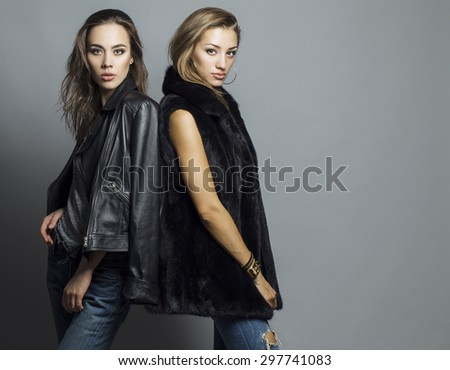 Fashion shot of two elegant beautiful girls (brunette and blonde) in studio on grey background, dressed in casual clothes . Shopping inspiration - stock photo