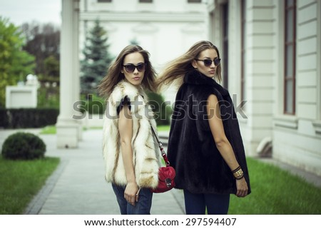 Fashion shot of two elegant beautiful girls in the sunset wearing sunglasses, fur vests . Two young women outdoor on the street. Shopping inspiration - stock photo