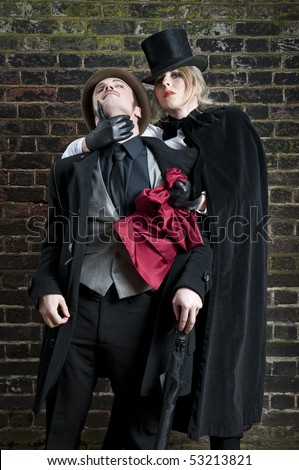 Fashion shot of woman  dressed as Jack the Ripper stealing man's handkerchief. - stock photo