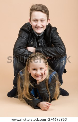fashion smiling european little long hair blonde girl and her brother posing in atelier - stock photo