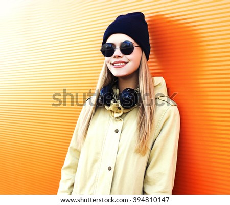 Fashion smiling girl in black style with headphones listens to music over colorful background - stock photo
