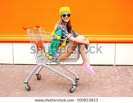 Fashion smiling hipster woman having fun wearing a sunglasses with skateboard sitting in the shopping trolley cart outdoors - stock photo