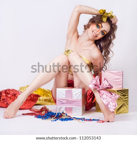 fashion smiling woman model with beauty bright make-up posing in studio with presents - stock photo
