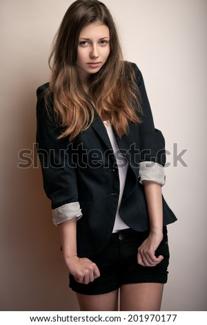 Fashion studio lifestyle portrait of a pretty young brunette model with long hair in black coat. - stock photo