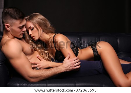 fashion studio photo of beautiful couple. gorgeous woman with long blond hair posing with handsome brunette man with sportive muscular torso  - stock photo