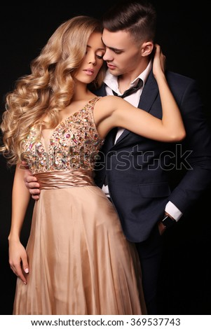 fashion studio photo of beautiful couple in elegant clothes, gorgeous woman with long blond hair embracing handsome brunette man  - stock photo