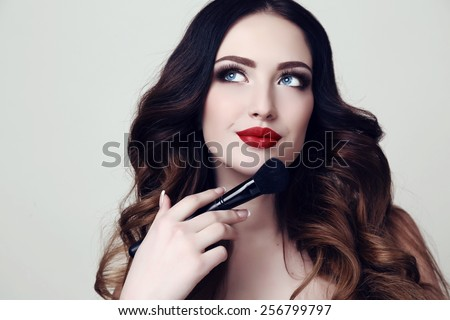 fashion studio photo of beautiful sensual woman with dark hair and bright makeup, holding makeup brush in hand - stock photo