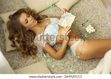 fashion studio photo of beautiful sexy woman with long blond hair in lingerie, posing among holidays presents - stock photo