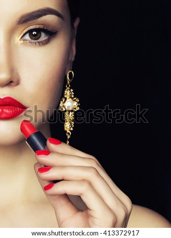 Fashion studio photo of beautiful young lady apply red lipstick. Perfect face makeup. Beauty and jewelry - stock photo