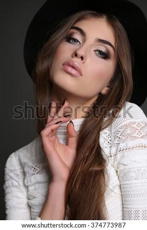 fashion studio photo of gorgeous sensual woman with dark straight hair wears elegant clothes,black hat and bijou   - stock photo