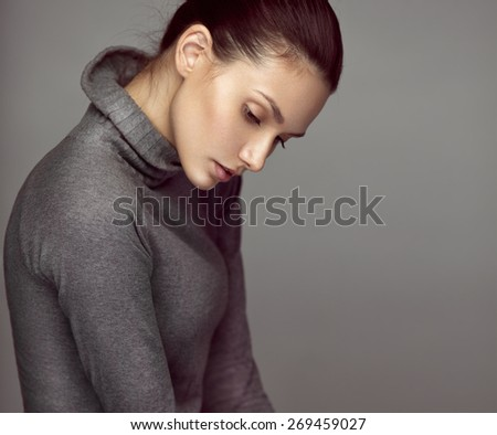 Fashion studio portrait of a young sensual brunette model in gray roll neck jumper. Looking down. - stock photo