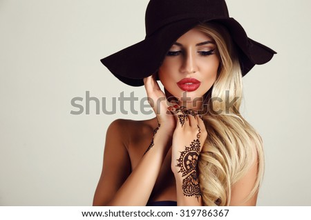 fashion studio portrait of beautiful sensual woman with blond hair with evening makeup and henna tattoo on hands  - stock photo