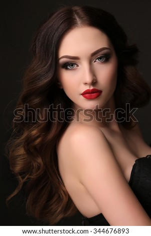 fashion studio portrait of gorgeous woman with luxurious dark hair with evening makeup - stock photo