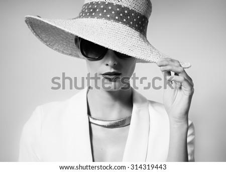 Fashion studio portrait of woman wearing hat. - stock photo