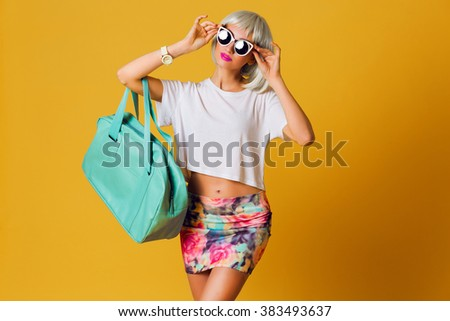 Fashion studio portrait  unusual pretty blonde girl in short party wig , white top and sexy skirt posing indoor on yellow background . Sunny positive  emotions, stylish sunglasses.  - stock photo