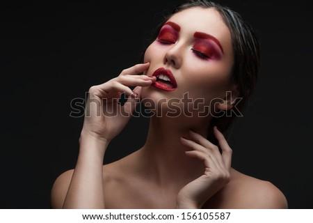 Fashion studio shot of beautiful woman with stylish red makeup and manicure - stock photo