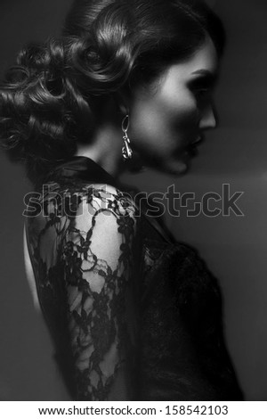Fashion studio shot of  beautiful young woman with retro hairstyle and elegant earrings - stock photo