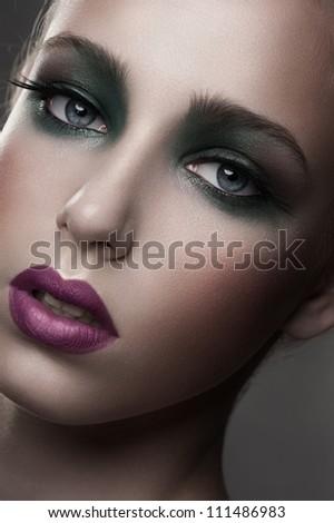 Fashion studio shot of young beautiful woman with stylish bright makeup - stock photo
