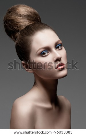 Fashion studio shot of young beautiful woman with stylish makeup and creative hairstyle - stock photo