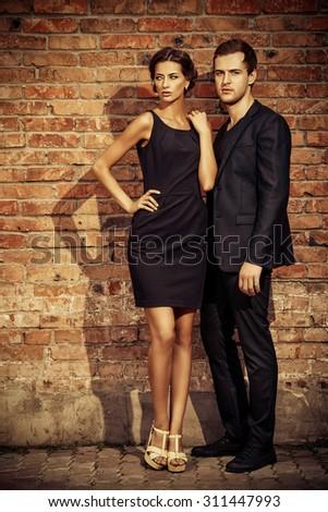 Fashion style photo of a beautiful couple over city background.  - stock photo