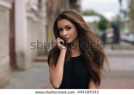 Fashion style portrait of young beautiful elegant woman in black dress walking at city streets on a windy dull day. - stock photo