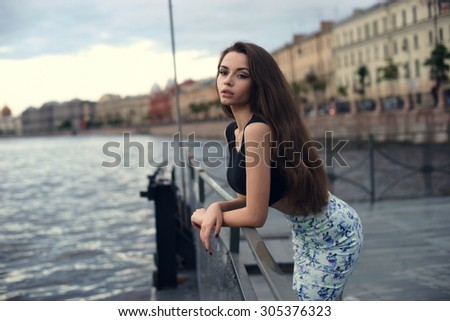 Fashion style portrait of young beautiful trendy hipster girl. Calm, thoughtful woman posing at small city pier or berth on a summer evening - stock photo