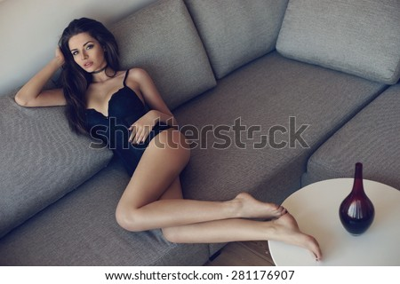 Fashion style portrait of young woman lying on sofa. Pretty sexy model posing with long legs posing in simple interior - stock photo