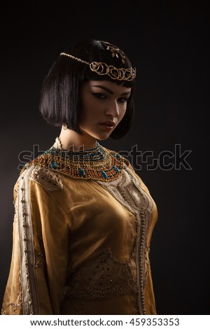 Fashion stylish beauty woman with black short haircut and professional make-up of Cleopatra over black. Beautiful girl's face in dark close-up. - stock photo