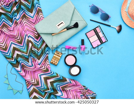Fashion stylish clothes, cosmetics, makeup accessories set. Urban summer girl colorful outfit. Stylish handbag clutch, trendy pants, necklace sunglasses. Woman essentials. Unusual overhead, top view. - stock photo