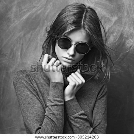 Fashion stylish woman. hipster in sunglasses on dark gray dirty background - stock photo