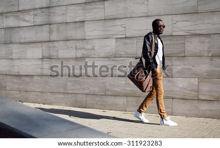 Fashion stylish young african man in sunglasses and black rock leather jacket with bag walking over grey textured city background - stock photo