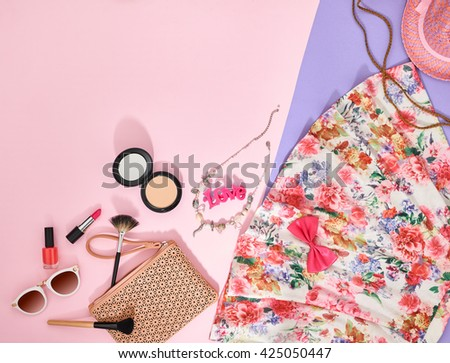 Fashion summer girl clothes accessories set. Woman essentials. Cosmetics, makeup. Stylish beige handbag clutch, trendy dress, necklace, sunglasses . Unusual overhead outfit, top view on pink - stock photo