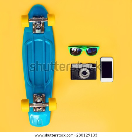 Fashion summer look concept. Blue skateboard, green sunglasses, vintage camera and screen smartphone on a yellow background, top view. Trendy colorful photo - stock photo