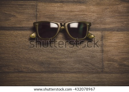 Fashion sunglasses on wooden table. Top view. Place for text. Toned photo. - stock photo