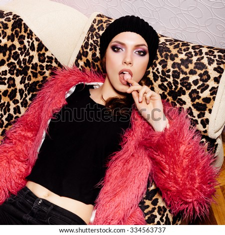 Fashion swag female model wearing black dress and beanie and pink fur coat licking candy. Freak young sexy Woman lying on leopard sofa. Vogue style indoors shot  - stock photo