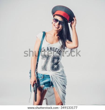 Fashion swag sexy girl holding gun woman having fun wearing police cap - stock photo